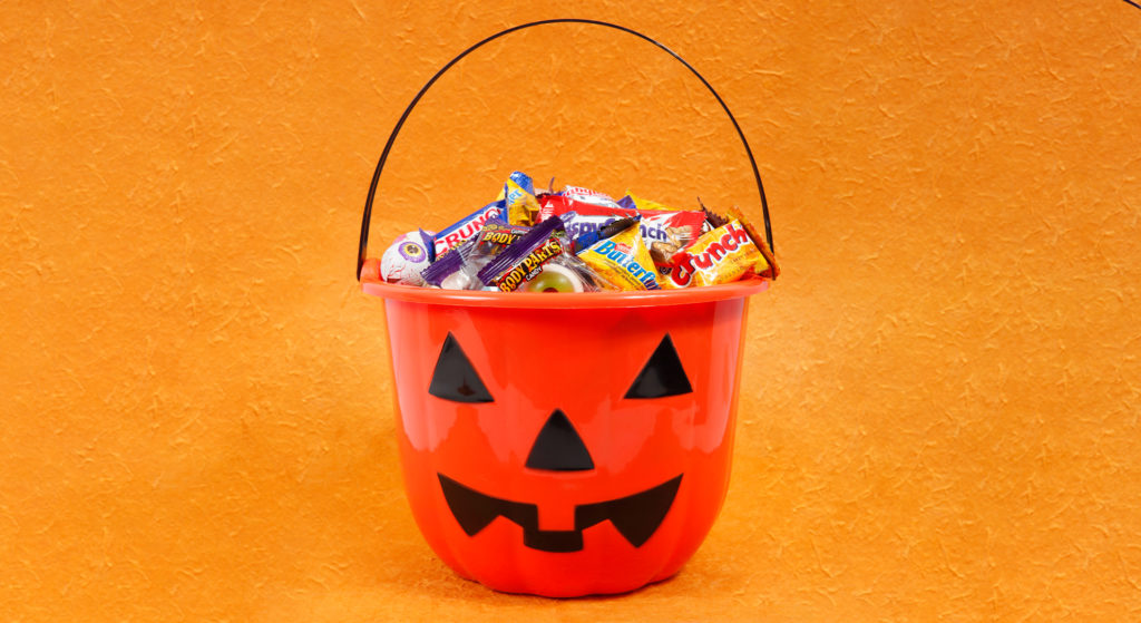 a plastic pumpkin with candy bars in it