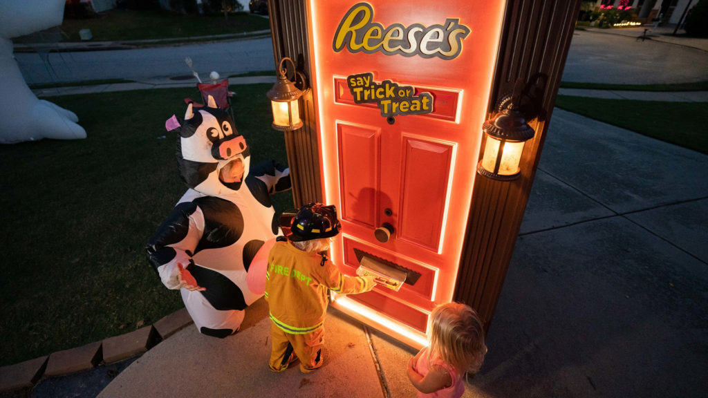 An orange door that says Reese's say trick or treat with a kid dressed as a firefighter and a cow and a ballerina taking something from the door's mail slot