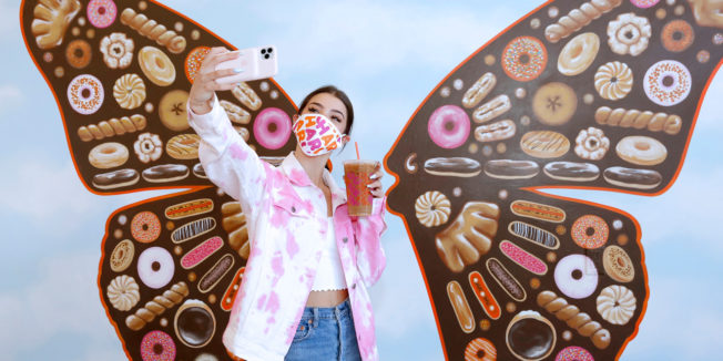 a woman standing in front of a mural of butterfly wings in a pink mask taking a selfie with a dunkin' cup