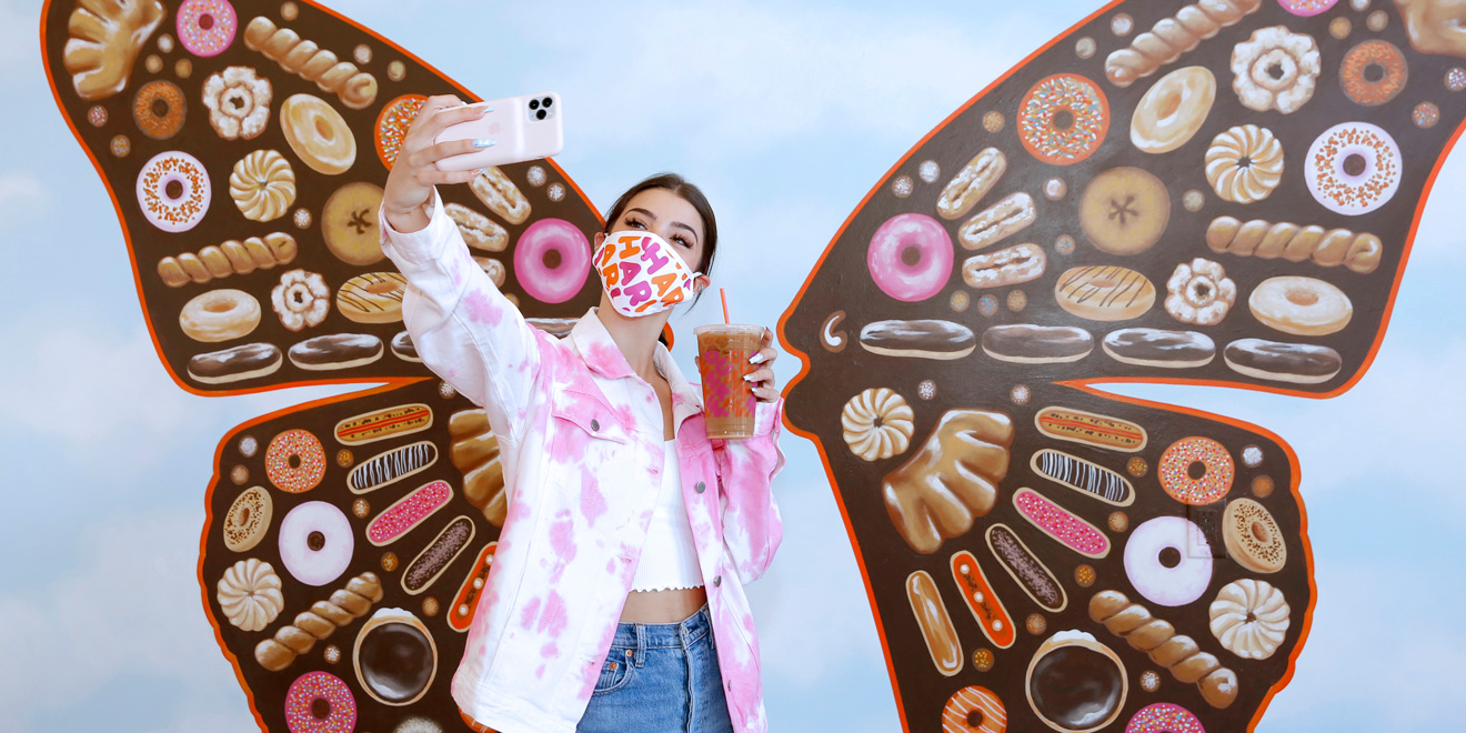 a woman standing in front of a mural of butterfly wings in a pink mask taking a selfie with a dunkin