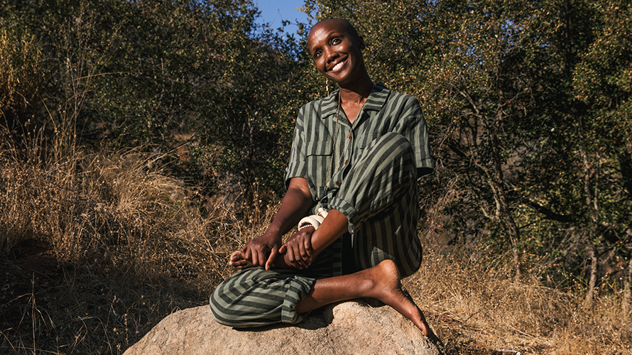 a black woman sitting on a rock in a wooded area