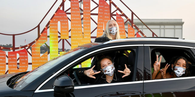 a girl in a car flashing hand signs while wearing a mask and another girl stands behind her in front of a roller coaster while also wearing a mask