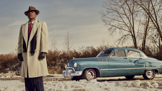 a man standing in front of an old blue car