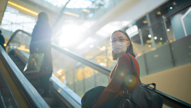 a woman in a mask on an escalator