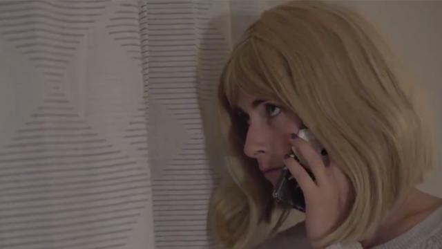 woman in a blonde wig on a phone