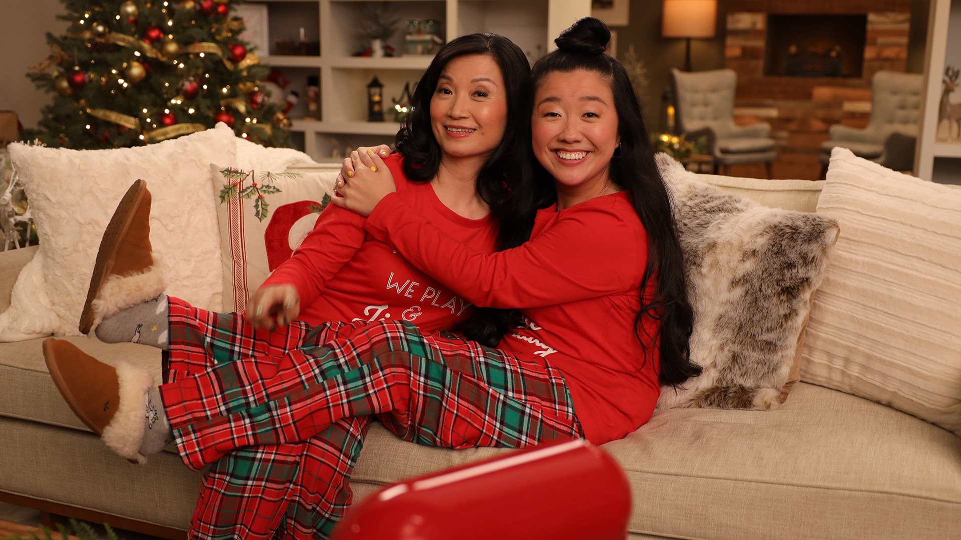 an asian mom and her daughter sitting on a couch dressed in red and hugging