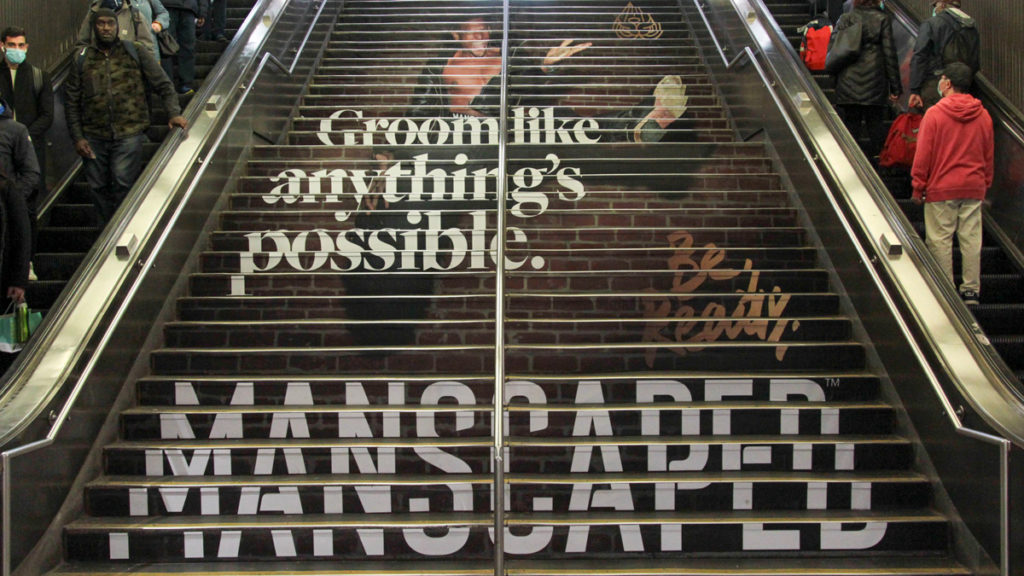 "An add on a staircase with a man jumping that says ""Groom like anything's possible"" Manscaped as people go up and down escalators on either side."