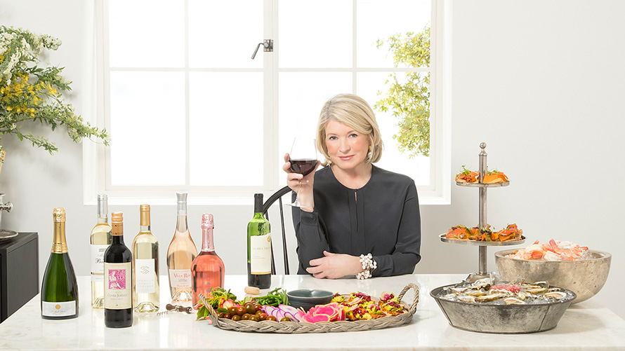 martha stewart sitting at a table holding a glass of red wine with bottles to her right and snacks like olives and oysters and shrimp to her left