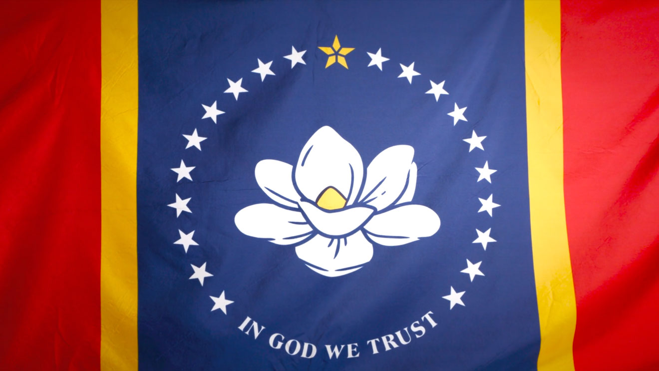 mississippi's new flag in red, yellow and blue with a magnolia surrounded by stars that says in god we trust at the bottom