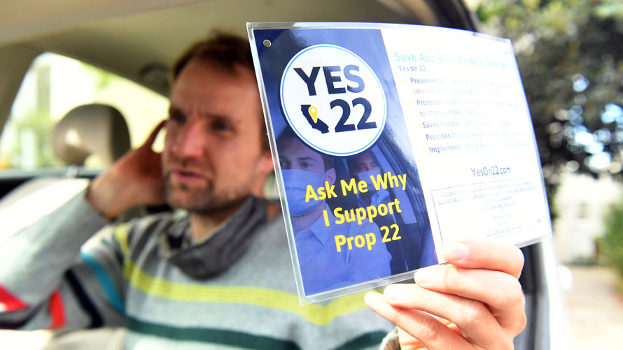 a driver holding a sign that says yes to 22 ask me why i support prop 22