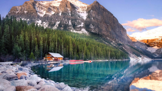 photo of a cabin next to a lake and mountainside