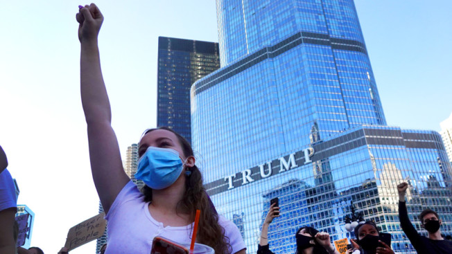 a masked woman standing with her fist in the air in front of a glass building