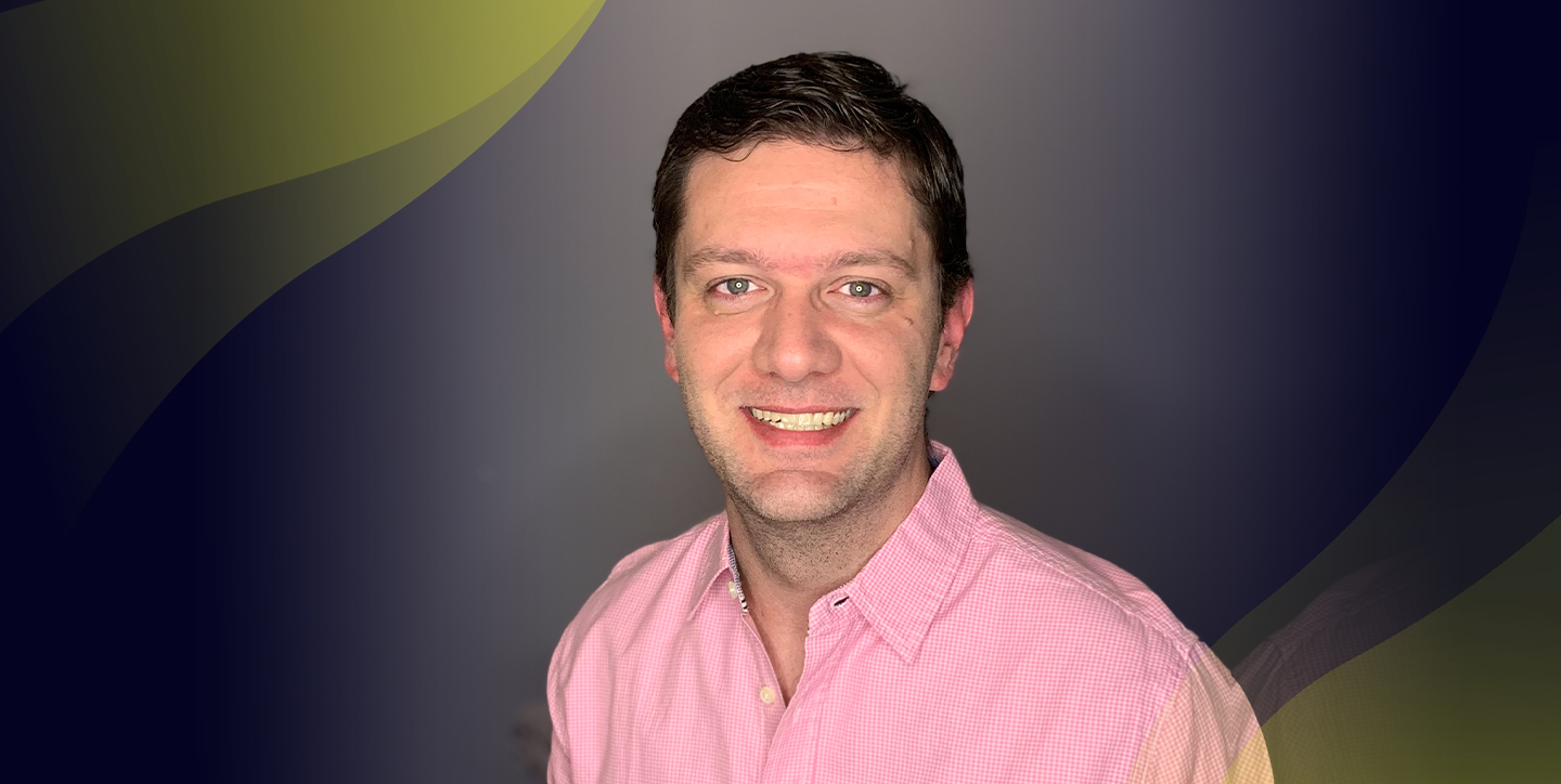 Man with brown hair, pink button down, against grew background with 1 yellow wave.