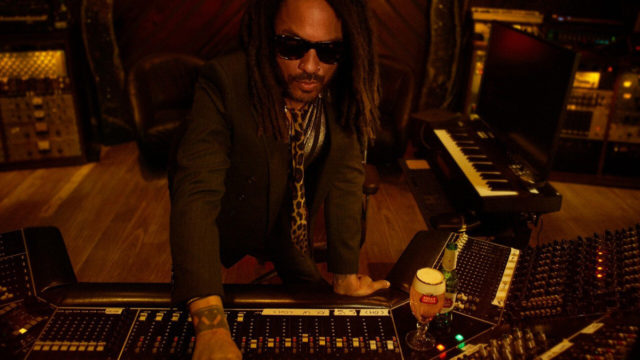 lenny kravitz with sunglasses on sitting at a keyboard