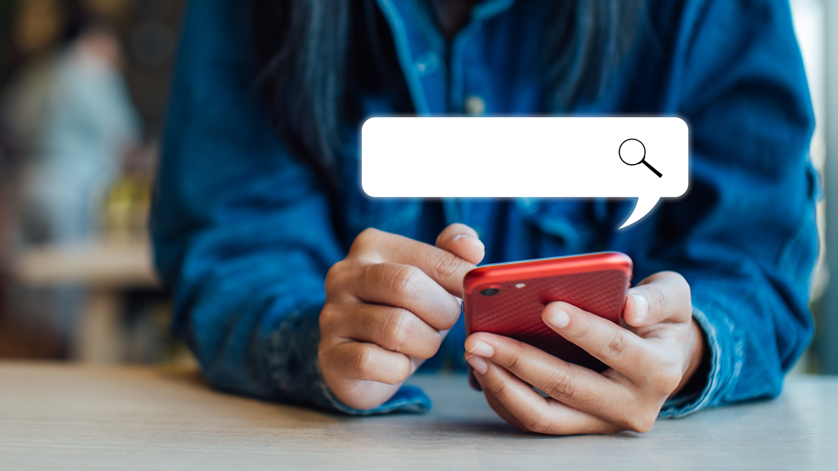 hands on a red phone with a search bar above it