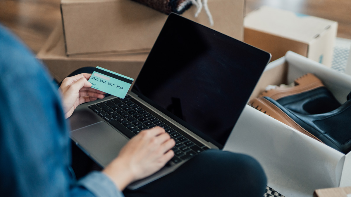 overhead of a person on a laptop with a credit card in their hands