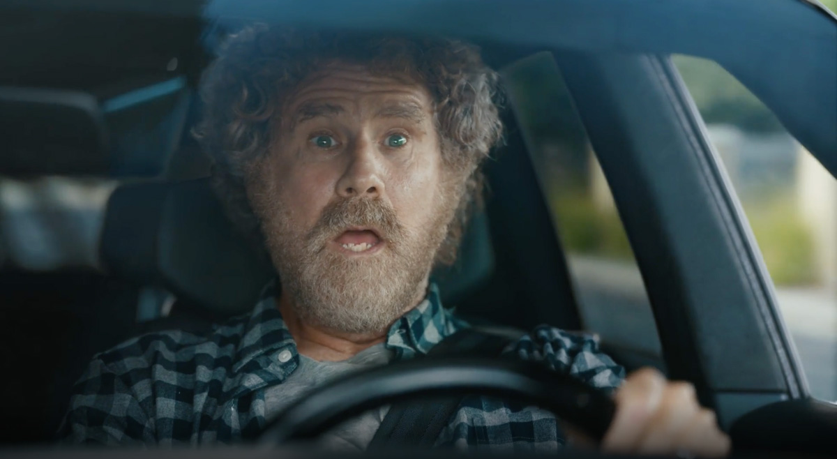 will ferrell looking shocked behind a steering wheel
