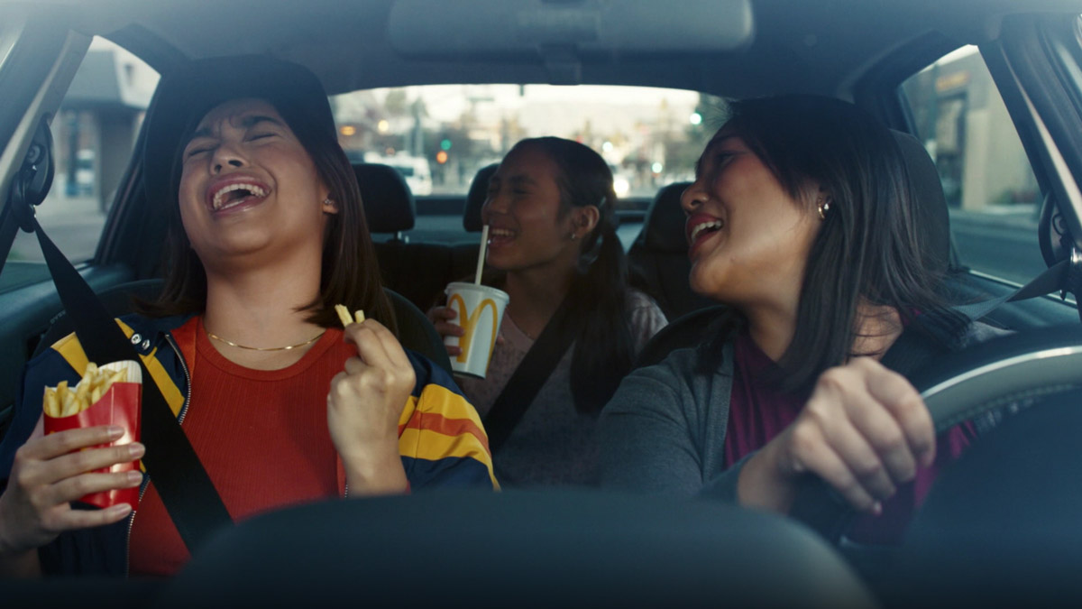 people singing passionately in a car holding mcdonald's