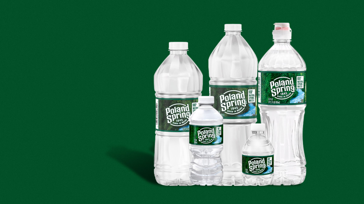 various sized bottles of poland spring water on a green background