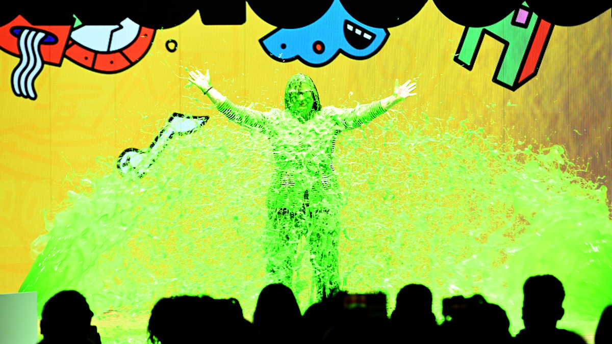a person covered in green slime with their arms wide open on a stage
