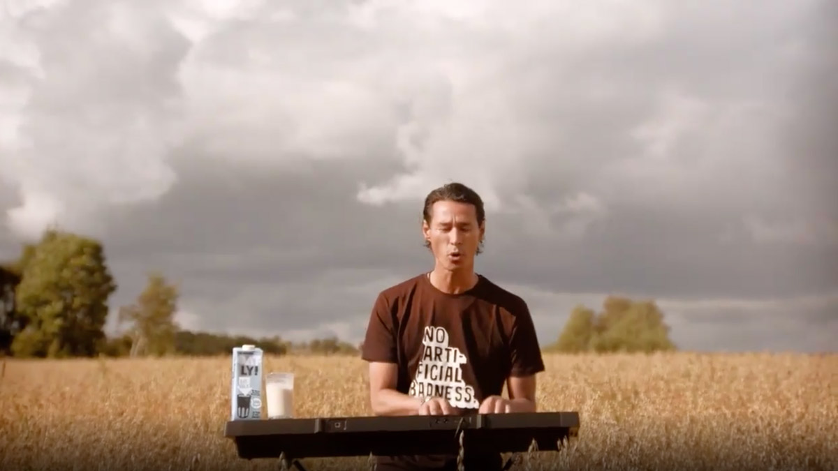 a man sitting in a field on a cloudy day drinking oatly oat milk