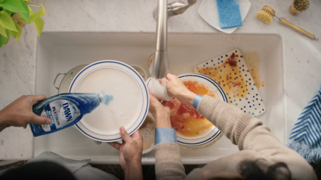an overhead shot of hands cleaning dirty dishes in a sink with blue dawn dish soap