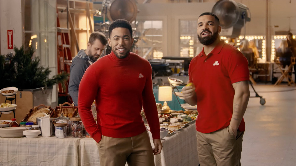 drake standing next to jake from state farm in red shirts and brown khakis
