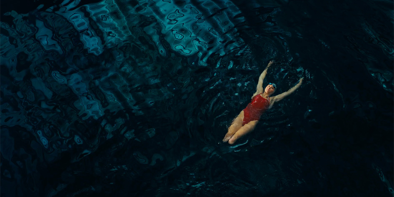a woman with no legs floating in a large pool of water