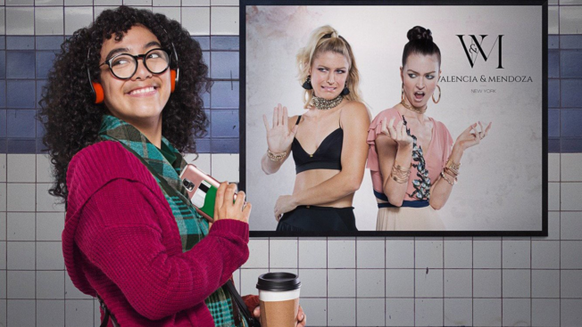 a girl with curly hair, glasses and headphones on in front of a poster
