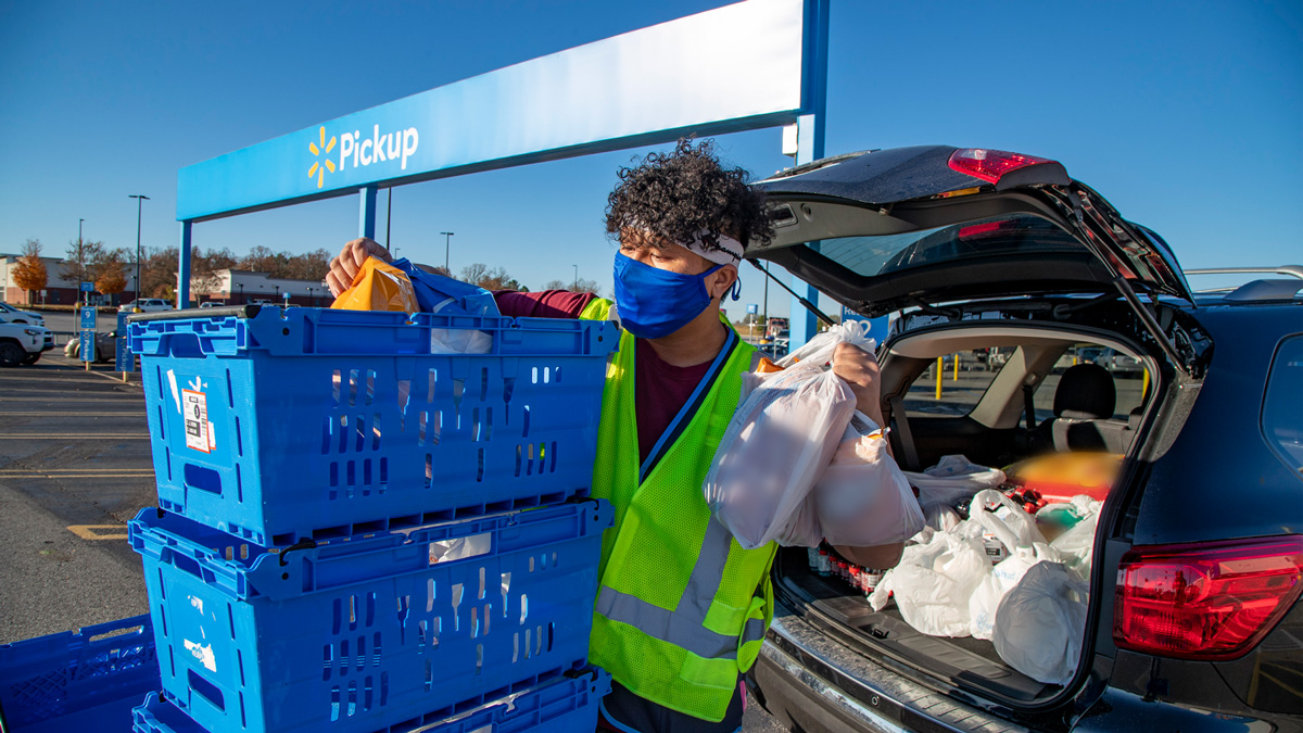 a walmart employee in a green vest unloading groceries into a car