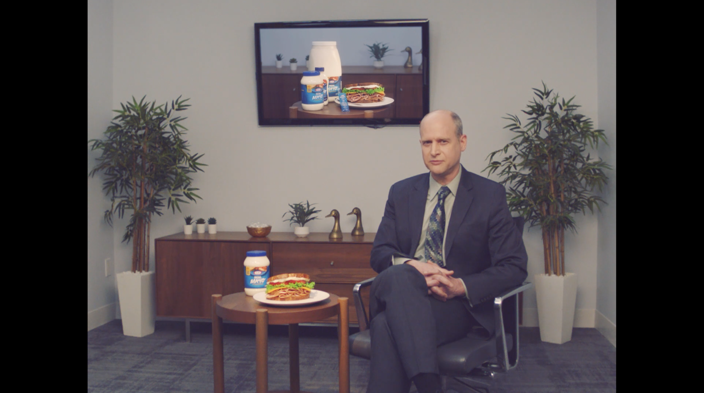 a man sitting in a chair with a sandwich and jar of mayo on the table beside him