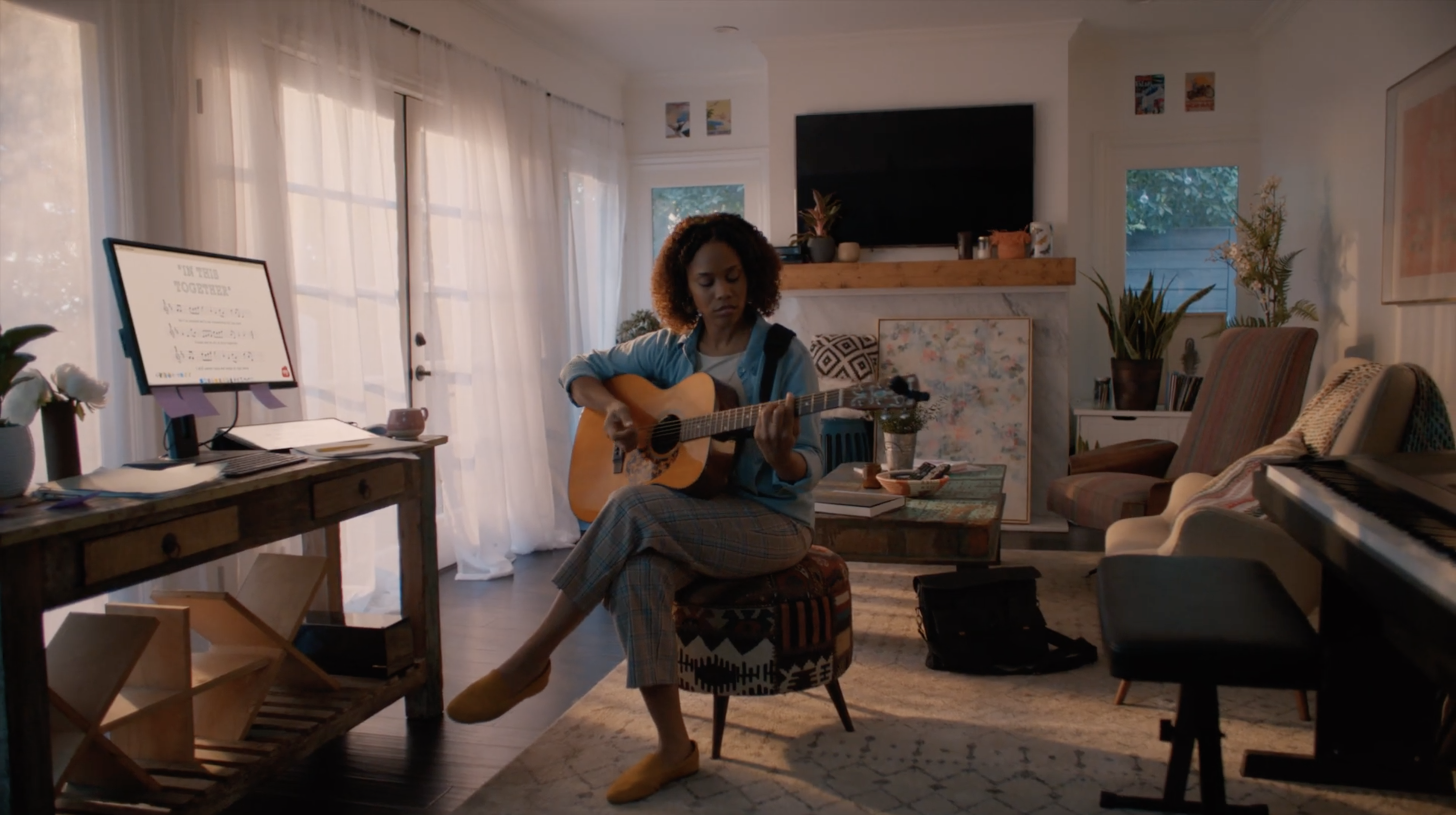 a woman playing guitar in her living room