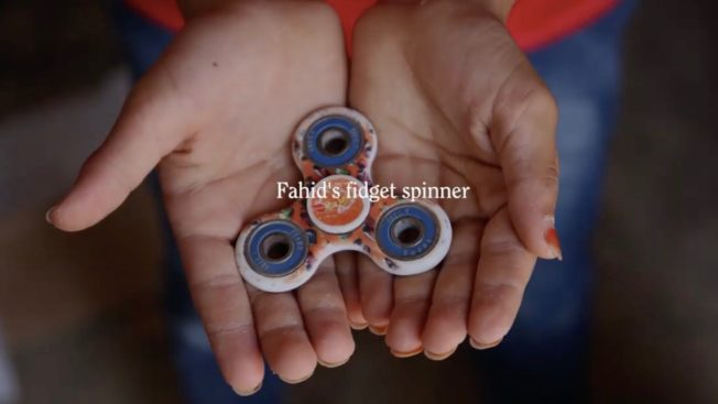 a kids hands with a fidget spinner in its open palms