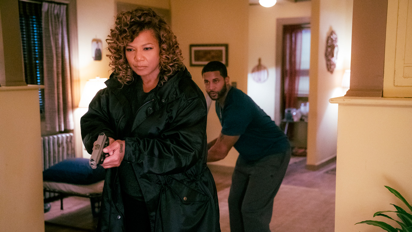 queen latifah holding a gun and walking in a room with a man behind her