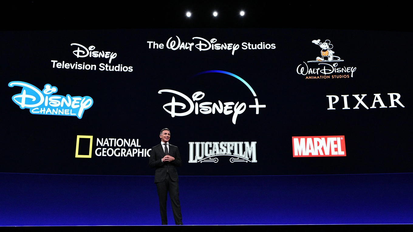disney+, disney, pixar, marvel, the walt disney company, national geographic and lucas films logos on a screen behind a man standing on a stage