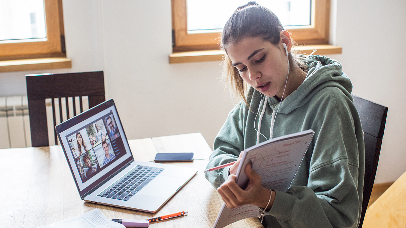 A female college student takes part in a class via video chat