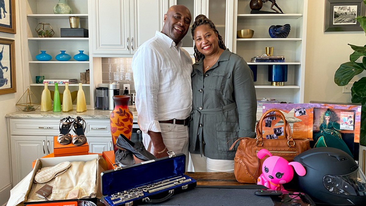 a photo of a man and woman posing in their home with items they intend to sell