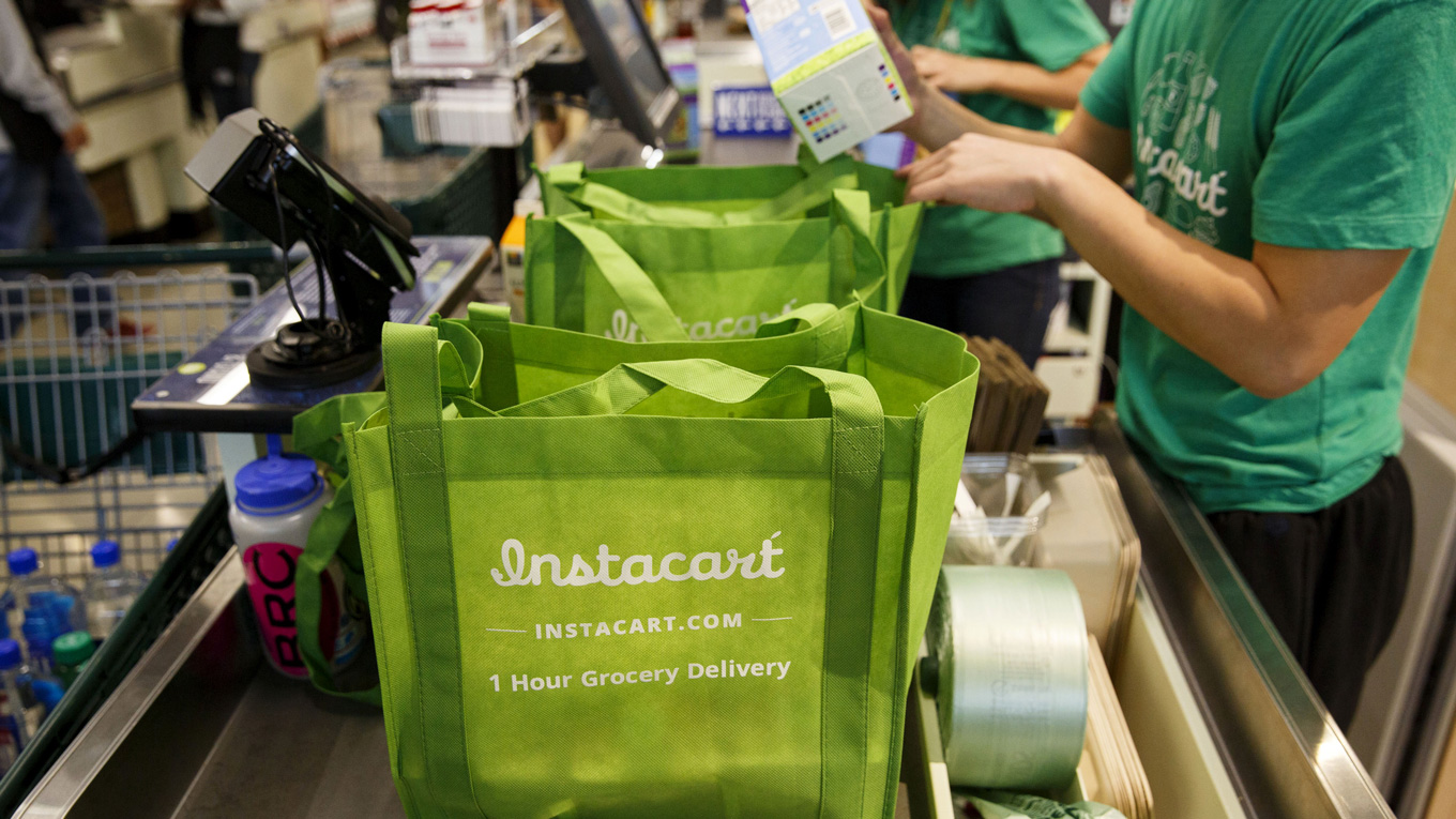 people putting groceries into a gree instacart bag