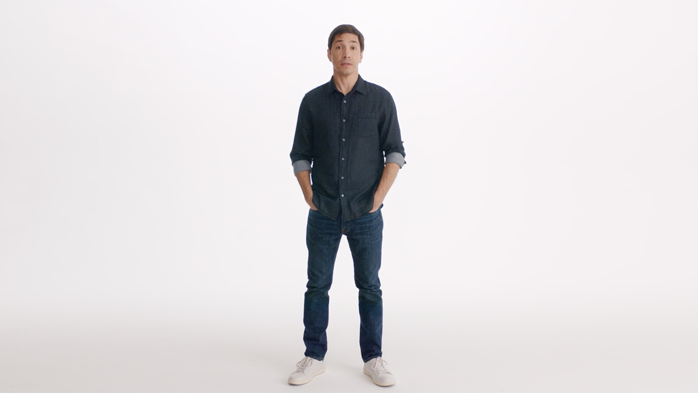 Actor Justin Long stands in front of a white background