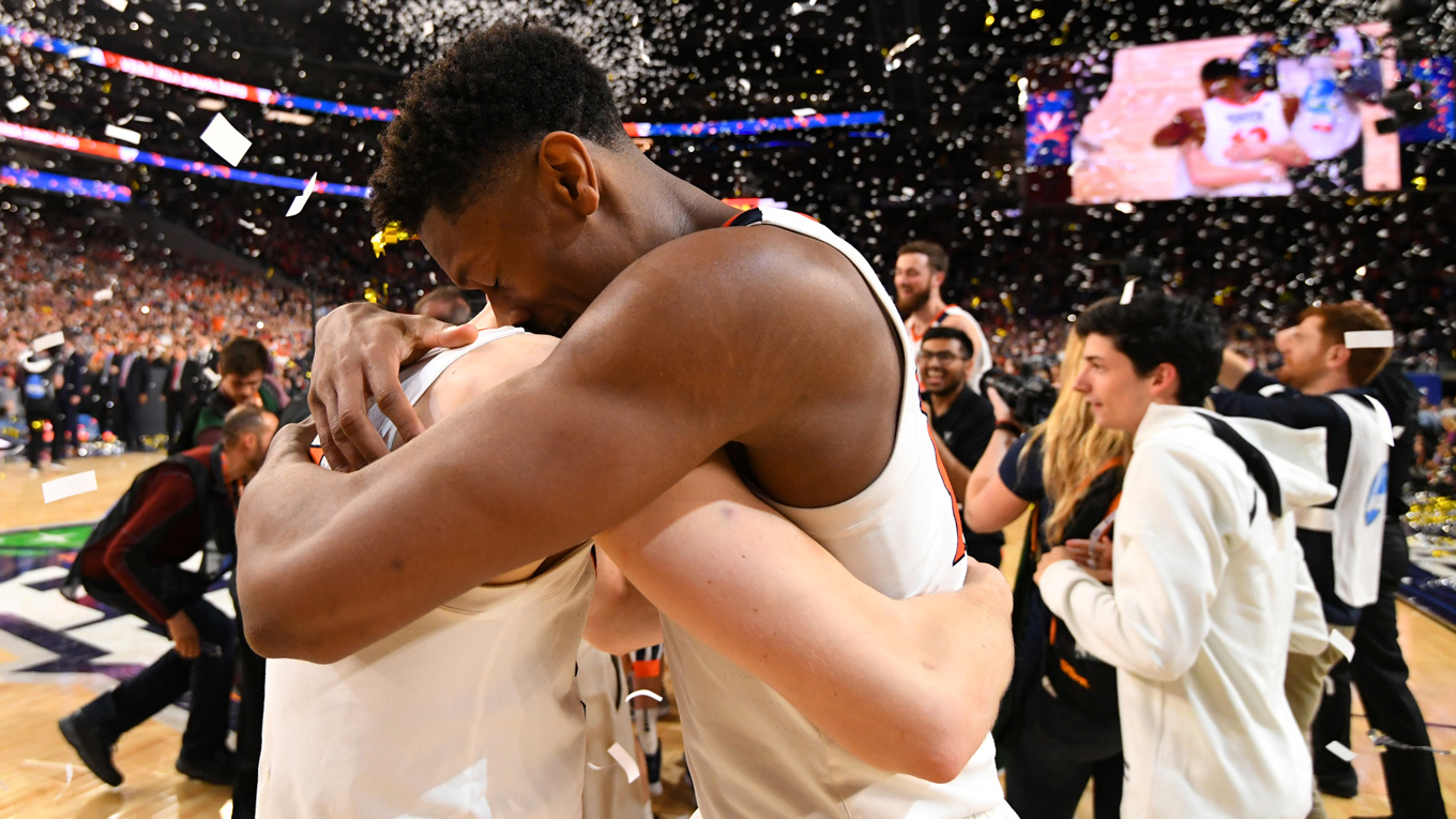 two basketball players hugging each other on the court