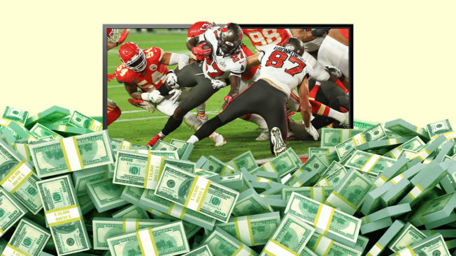 piles of cash on the floor and a flat-screen tv showing a game of football behind it