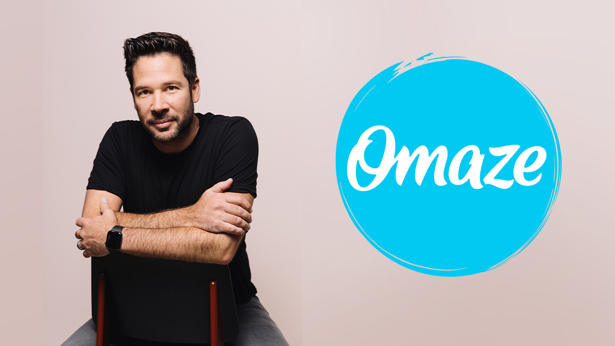 Eric Edge sitting on a chair with the Omaze logo right near him