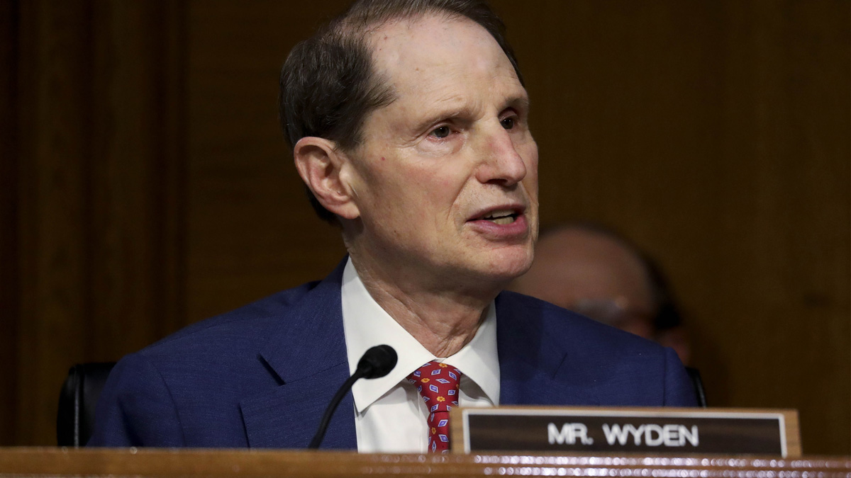 senator ron wyden speaking into a small microphone