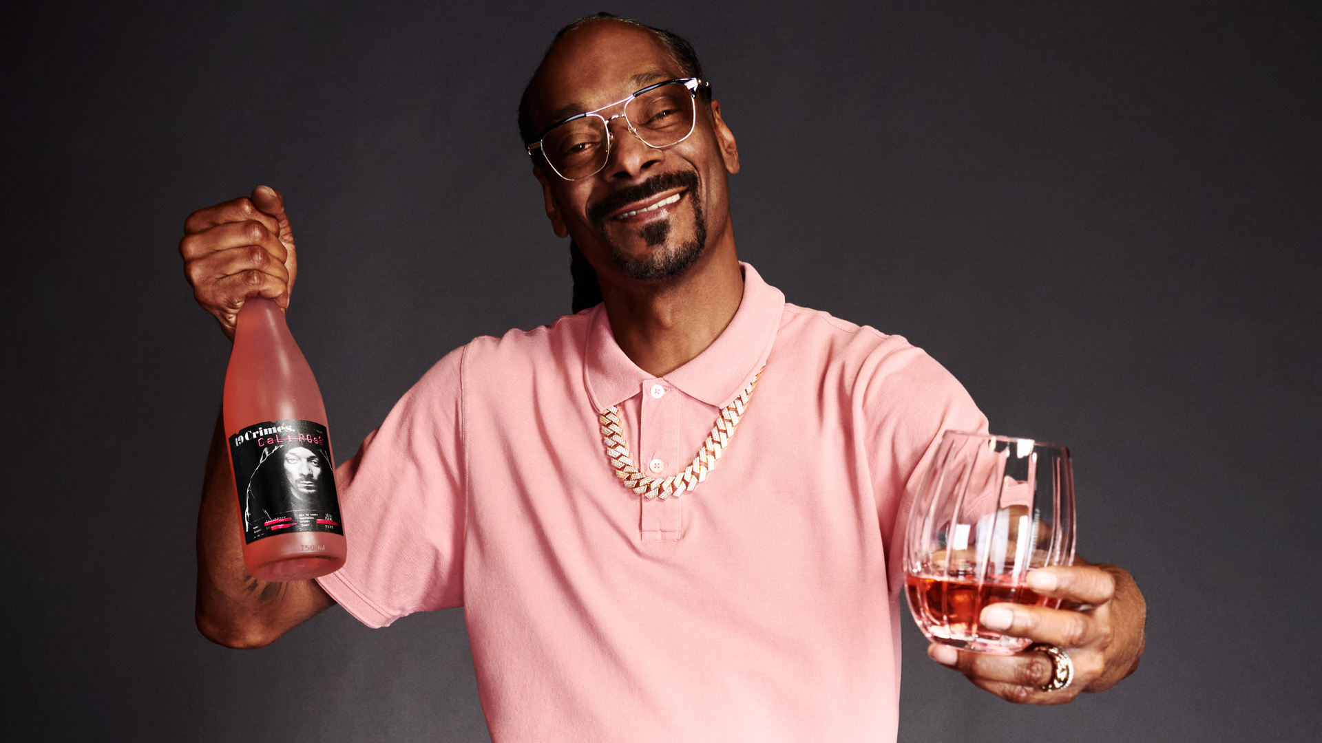 a photo of snoop dogg posing with a glass and bottle of his new brand of wine Snoop Cali Rosé