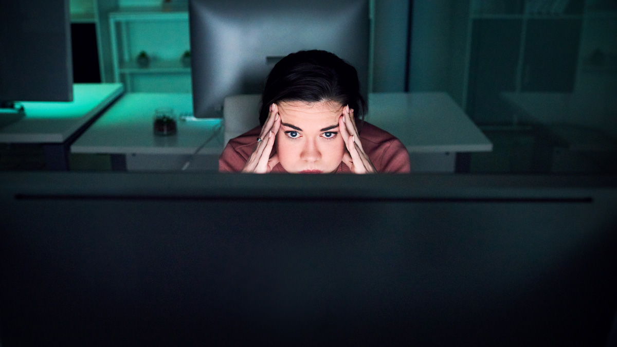 a women with her hands on her temple while starting at her computer screen