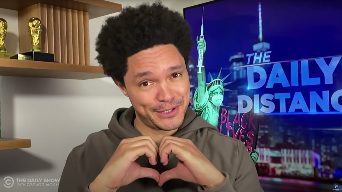 photo of daily show host trevor noah making a hear with his hands and smiling