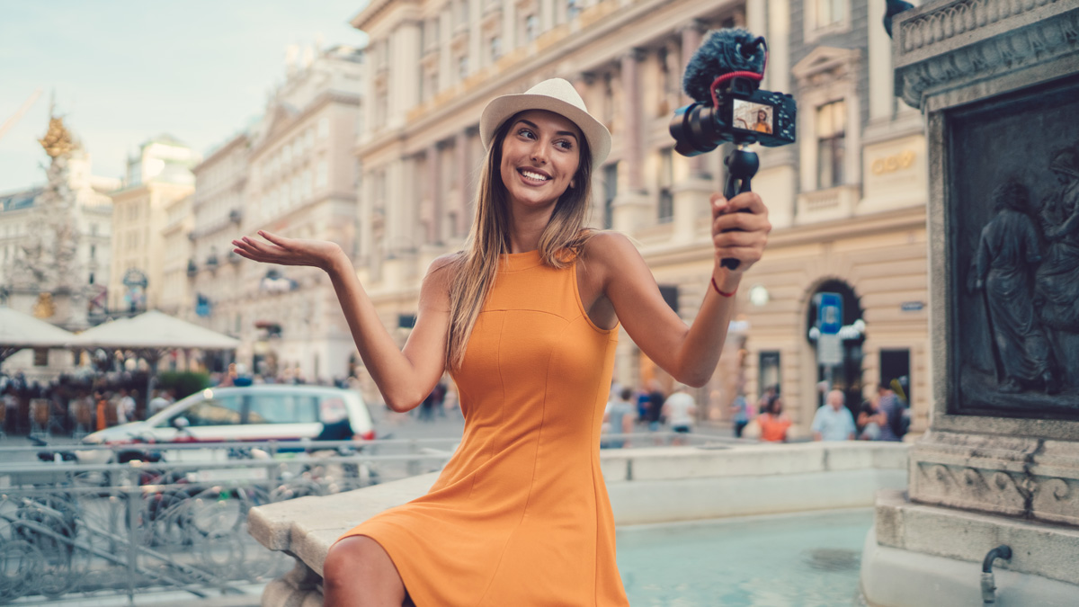 a woman in an orange dress shrugging and holding her hand out while pointing a camera at herself