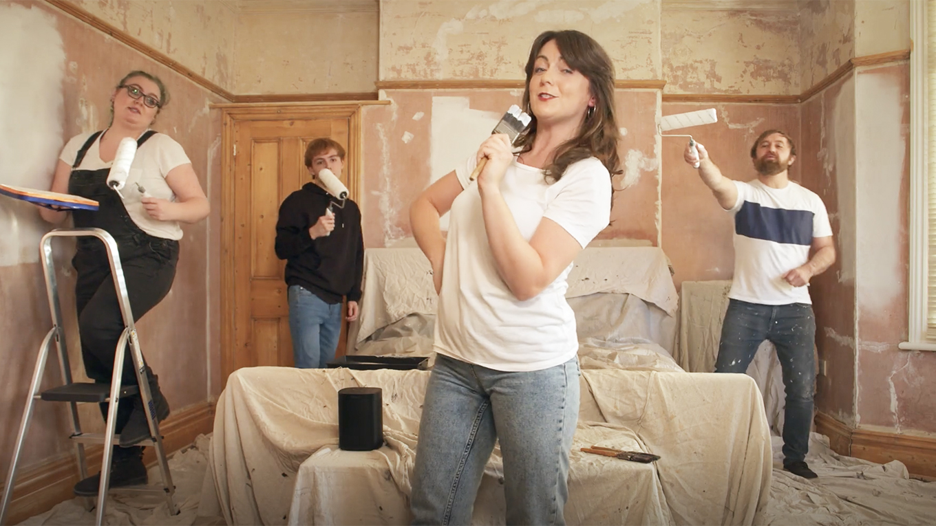a woman singing into a paintbrush and several people painting behind her