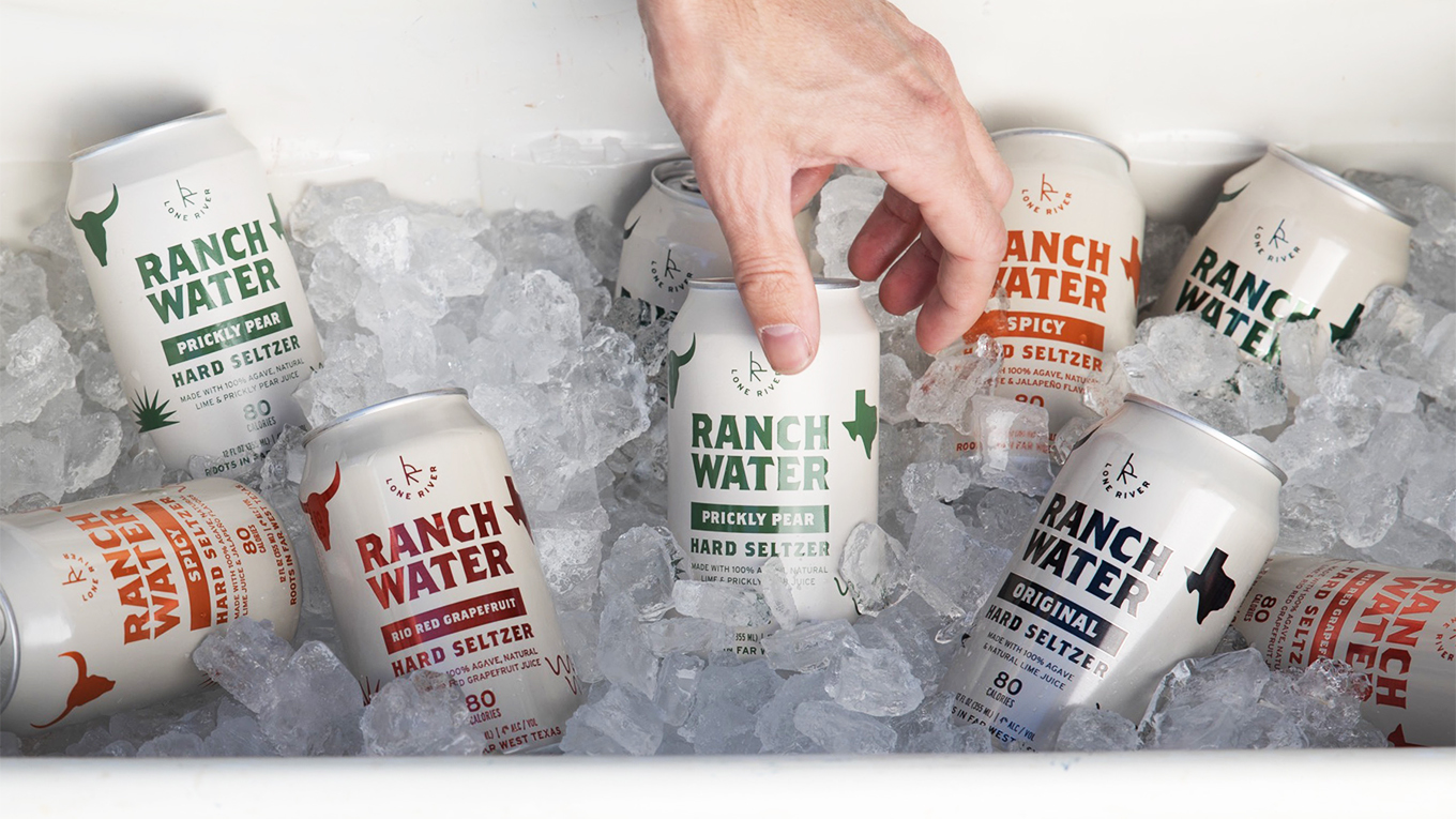 A hand reaches into a cooler full of ice and cans of Lone River Ranch Water