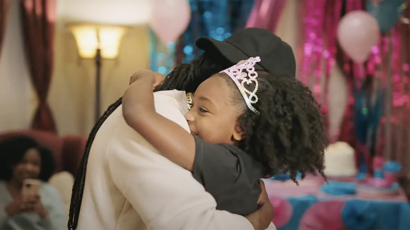 A still from a P&G ad featuring a young girl and an adult hugging